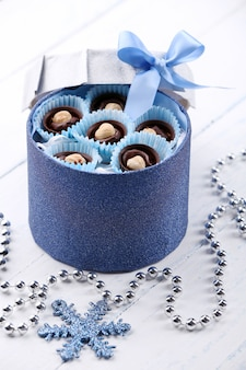 明るい木製の背景に弓とギフトボックスのチョコレート菓子