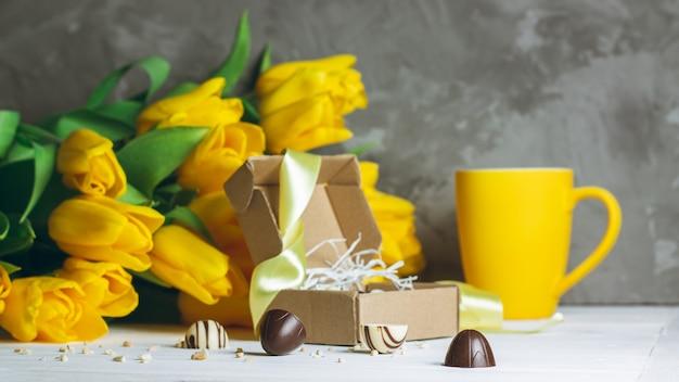 Шоколадные конфеты в крафт-коробке, чашка и букет желтых тюльпанов на белой деревянной поверхности