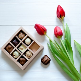 ボックスにチョコレート菓子。キャンディーボックスと白い背景の上のロマンチックなギフトのための赤いチューリップ