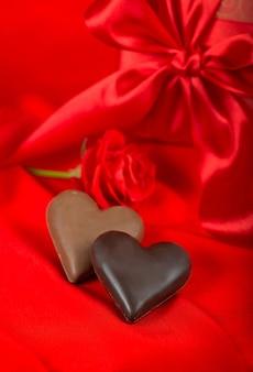 Шоколадные конфеты в форме сердца на красном фоне