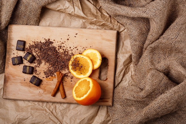 木製の机の上のチョコレートキャンディーオレンジとシナモン。