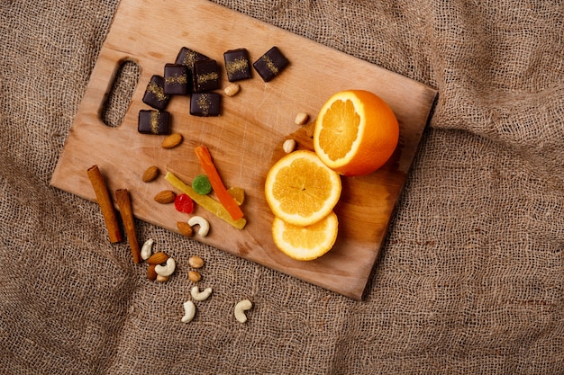 Chocolate candies orange cinnamon and nuts on wooden desk.
