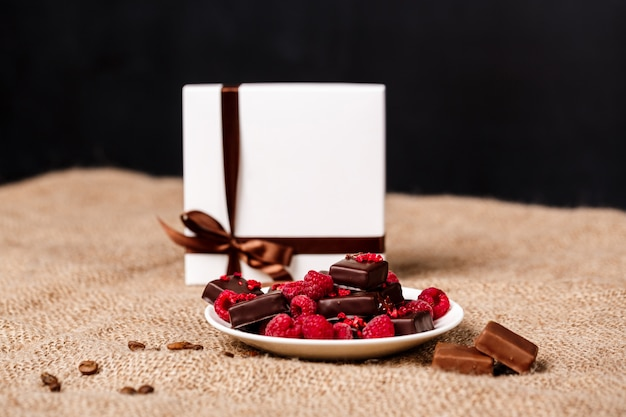 Chocolate candies and raspberry on white plate on sackcloth.
