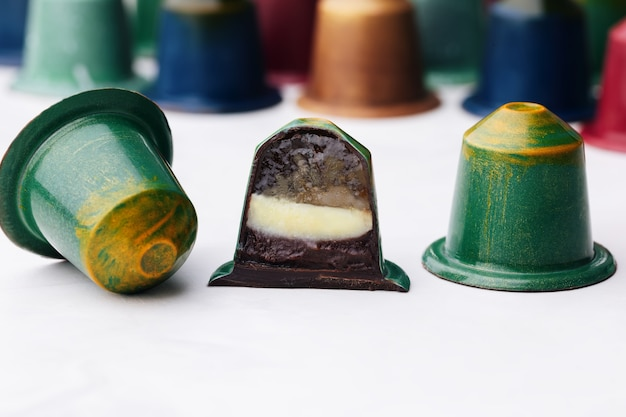 Chocolate candies in the shape of a coffee capsule with lime and mint jelly, raspberry ganache.