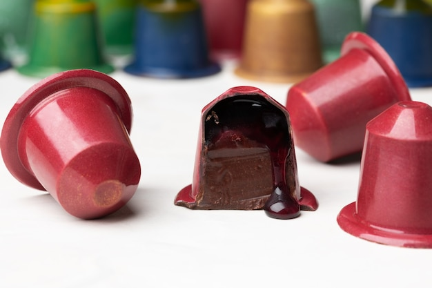 Chocolate candies in the shape of a coffee capsule with red wine filling.