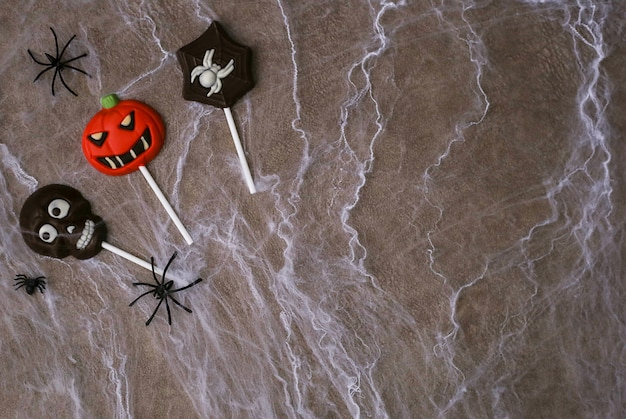 Chocolate candies in the shape of skull, jack pumpkin and spider on background of cobwebs. halloween concept