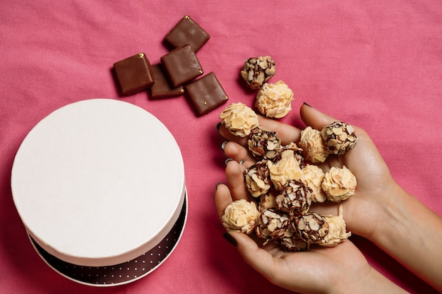Chocolate candies in woman's hands on pink