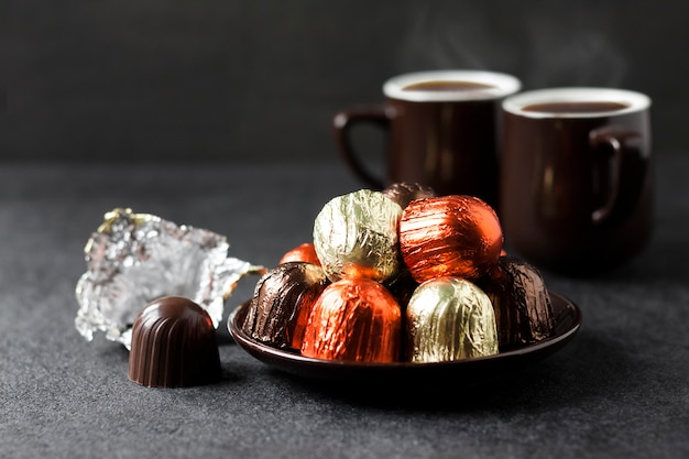 Chocolate candies wrapped in multicolored foil and two cups of coffee on black surface