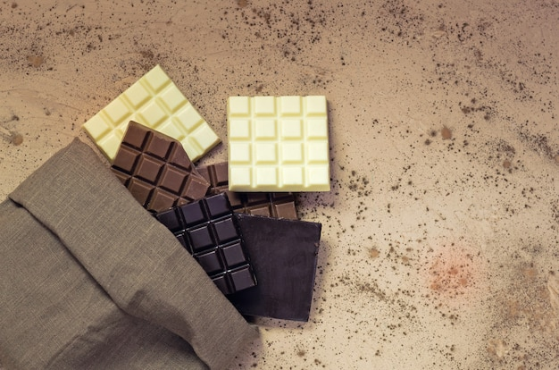 Chocolate candy bars. chocolate bar pieces. different milk and dark chocolate. chocolate pieces on wooden background.