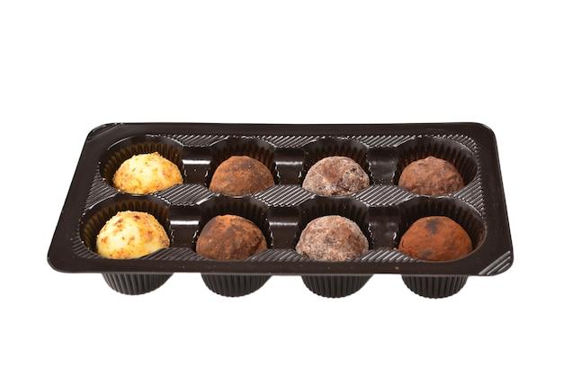 Коллекция шоколадных конфет в пластиковой коробке.