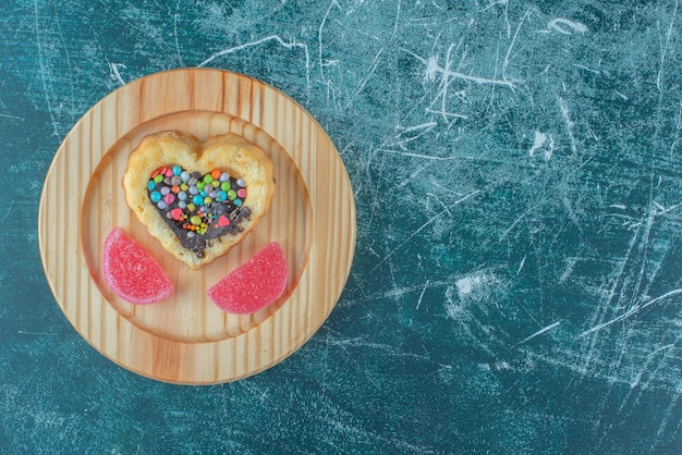 Chocolate and candy filled cake and marmelades on a wooden platter on blue background. high quality photo