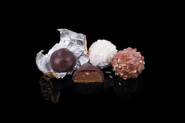 反射する黒い表面のチョコレート菓子さまざまな色と形