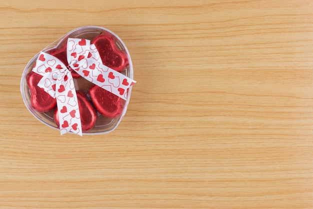 Chocolate candy red heart in gift box with ribbon on wooden background.