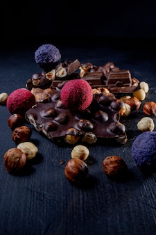 Трюфель шоколадных конфет с кусочками шоколада и летающим какао-порошком на темном фоне.
