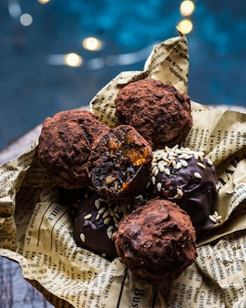 Chocolate candy truffle with chocolate pieces and flying cocoa powder on a dark background. healthy candy. vegan candy. new year dessert. christmas dessert. valentines day