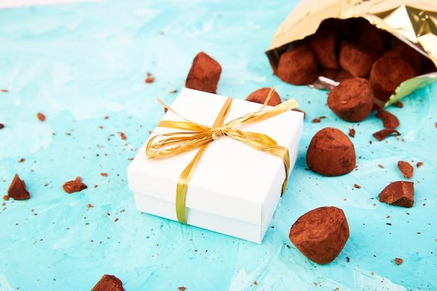 초콜릿 캔디 트뤼플이 황금색 고급 상자에서 떨어졌습니다.