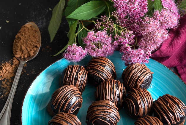 Chocolate candy truffles and pink flowers on dark background. delicious treat, sweet dessert.
