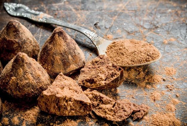 코코아 가루가 들어간 초콜릿 캔디 트뤼플. 나무 배경.