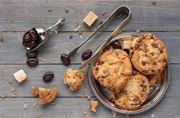 木製の背景にチョコレートチップクッキーとチョコレート菓子