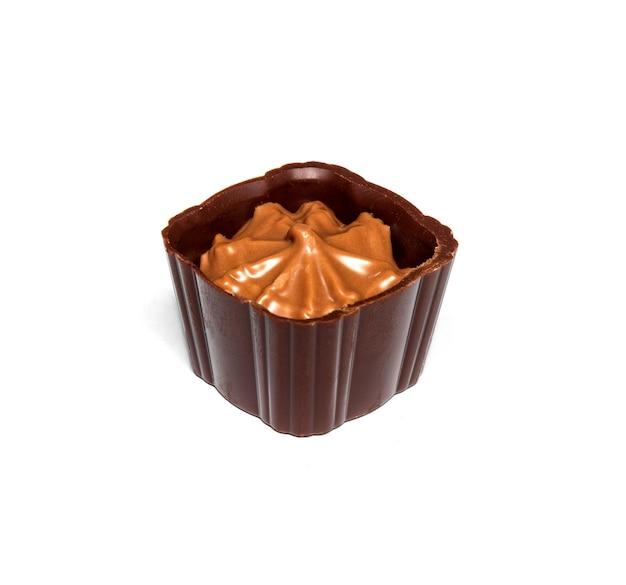 白い孤立した背景にクリームとチョコレート菓子。レストランでのデザートのアイデア