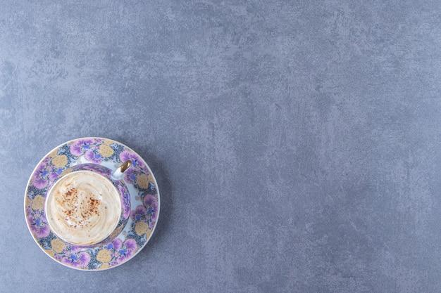 파란색 배경에 접시에 컵에 초콜릿 카푸치노. 고품질 사진