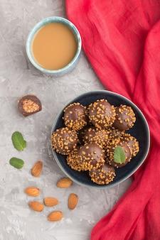 Шоколадно-карамельные шарики с миндалем и чашкой кофе на серой бетонной поверхности и красной ткани