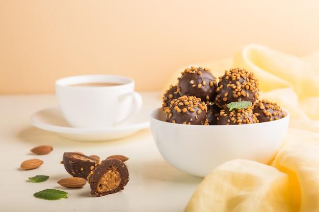 Шоколадно-карамельные шарики с миндалем и чашкой кофе на бело-оранжевой поверхности и желтой ткани