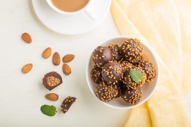 Шоколадно-карамельные шарики с миндалем и чашкой кофе на белой деревянной поверхности и желтой ткани
