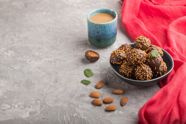 Chocolate caramel ball candies with almonds and a cup of coffee on a gray concrete background and red textile. side view, copy space.