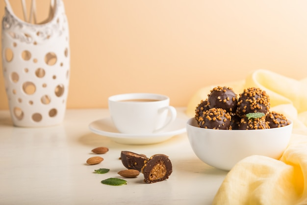 Chocolate caramel ball candies with almonds and a cup of coffee on a white and orange background. side view, copy space.