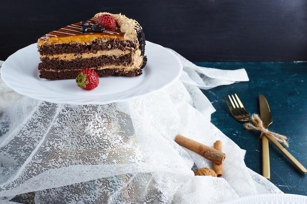 Ломтики шоколадного карамельного торта на белой тарелке.