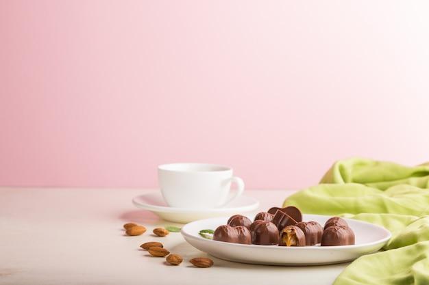アーモンドと白とピンクの背景の上にコーヒーを1杯とチョコレートキャラメルのお菓子