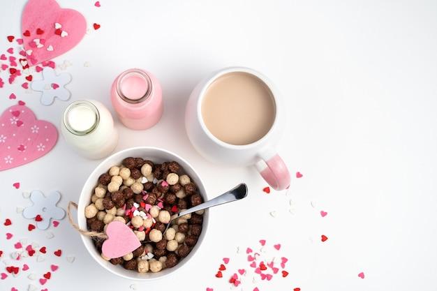白いボウルにチョコレートシリアルボールとロマンチックな背景に牛乳とコーヒーのカップ。バレンタインデーのコンセプト