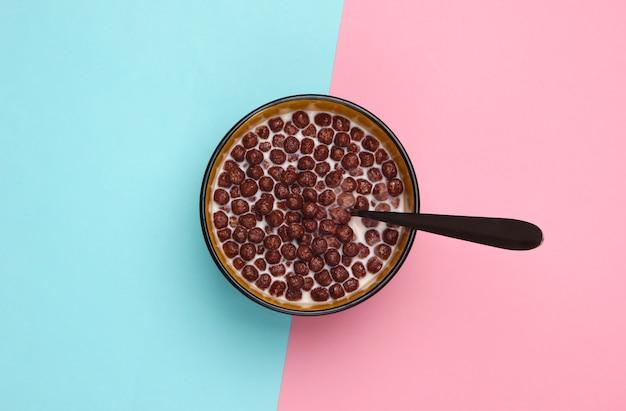 우유와 핑크 블루 파스텔에 그릇에 숟가락 초콜릿 시리얼 공. 건강한 식단에 대한 개념.