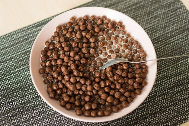 Chocolate cereal balls with milk in a bowl on napkin on wooden table.