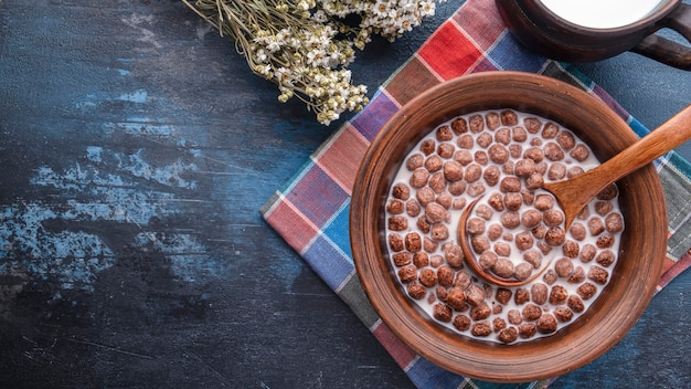 ボウルにミルクとチョコレートシリアルボール。健康的な朝食のコンセプト。スペースをコピーします。上面図