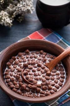 나무 테이블에 그릇에 우유와 초콜릿 시리얼 공. 맛있는 아침. 건강 식품 개념