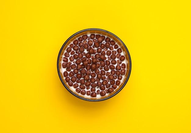 노란색 그릇에 우유와 초콜릿 시리얼 공. 건강한 식단에 대한 개념.