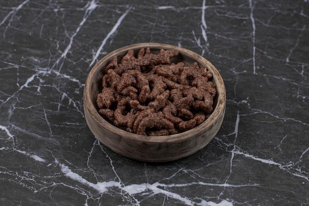 나무 그릇에 초콜릿 시리얼 조각입니다.