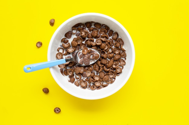 Chocolate cereal with milk on yellow