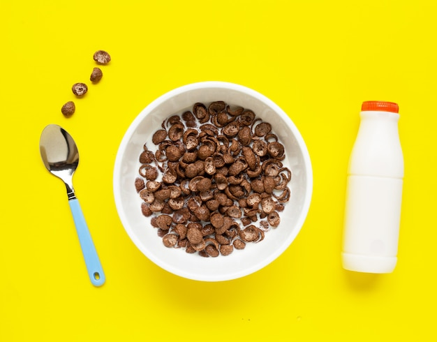 Chocolate cereal with milk on yellow.