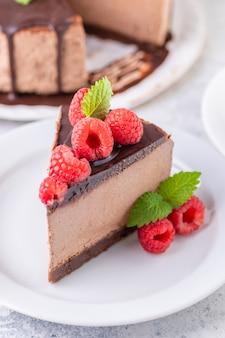 Шоколадный чизкейк со свежей малиной и листьями мяты. кусок торта отрезается и подается на тарелке. домашний десерт. крупный план.