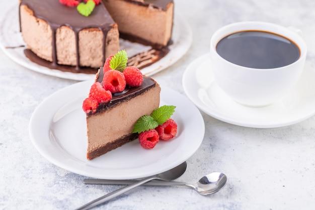 新鮮なラズベリーとミントの葉が入ったチョコレートチーズケーキ。ケーキを切って皿に盛り付けます。自家製デザート。閉じる。