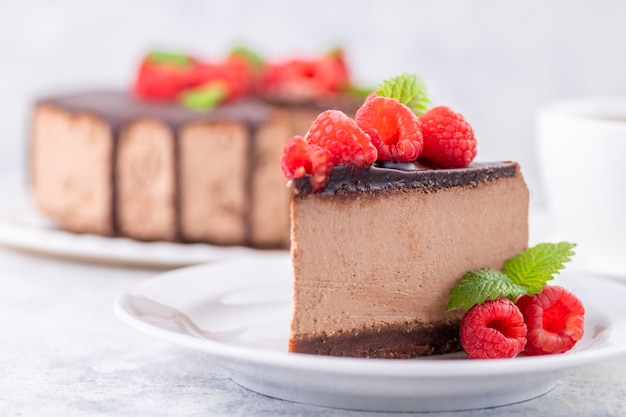 Chocolate cheesecake with fresh raspberries and mint leaves. a piece of cake is cut and served on a plate. homemade dessert. close-up.