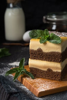 Chocolate cheesecake with vanilla filling on a dark background