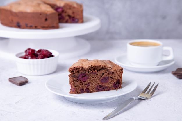Шоколадно-вишневый пирог на заднем плане - пирог, чашка кофе с вишнями и кусочки шоколада.