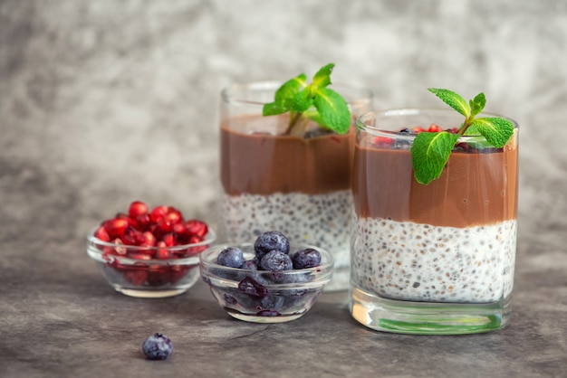Chocolate chia pudding in glass on grey background. with copy space