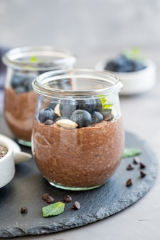 Chocolate chia pudding with blueberry, almonds and mint on top in a glass jar on a gray concrete background. healthy food. copy space.