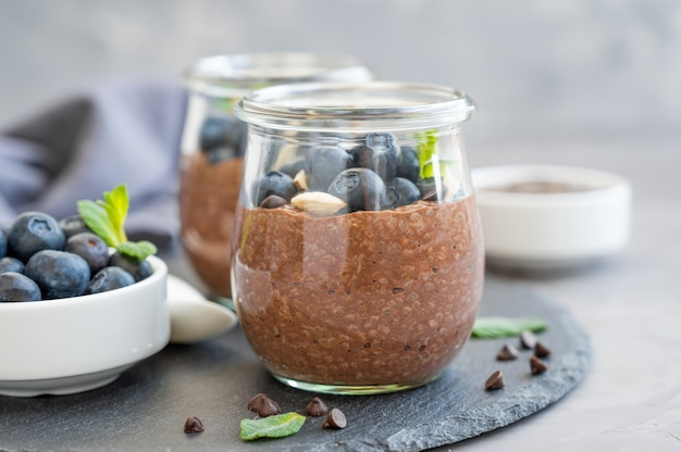 Chocolate chia pudding with blueberry, almonds and mint on top in a glass jar