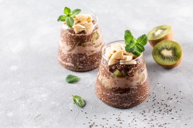 Chocolate chia pudding with kiwi and banana in glass on gray table